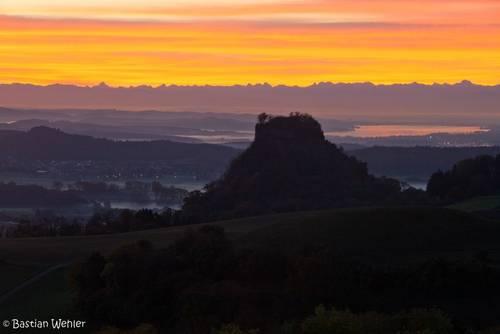 Ausblick kurz vor Sonnenaufgang vom Mägdeberg im Hegau über den Hohenkrähen Richtung Bodensee bis hin zu den Gipfeln der Alpen