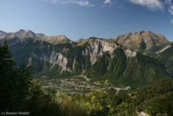Ausblick von der Straße hinauf nach Alpe d'Huez hinunter ins Tal auf den Ort Le Bourg-d'Oisans