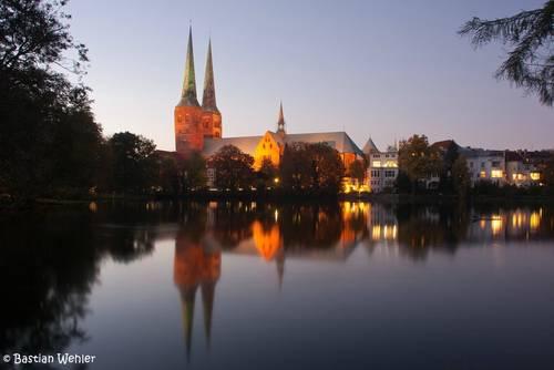 Blick in der Abenddämmerung über den Mühlenteich zum Lübecker Dom der sich auf dem Wasser spiegelt