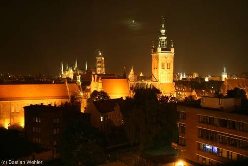 Blick über Danzigs Altstadt bei Nacht, die Katharinenkirche mittig, im Hintergrund die Marienkirche