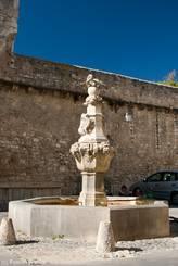 Der Brunnen Fontaine du Cormoran (18. Jahrhundert) nahe der Stadtmauer und dem Tor Notre-Dame von Pernes-les-Fontaines