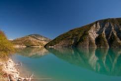 Der nördliche Teil des Lac de Castillon mit seinem grün-blauen Wasser und den Bergen im Hintergrund