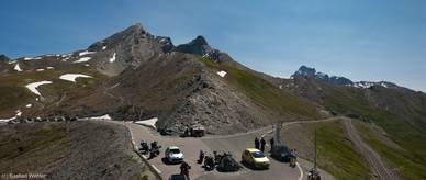 Die Passhöhe des Col Agnel mit ihrem kleinen Parkplatz und der Grenze zwischen Frankreich und Italien auf 2744 Metern Höhe, im Hintergrund die Berge Pain de Sucre, Pic d'Asti und Monte Viso