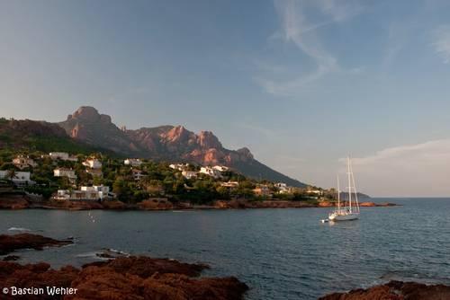Die roten Felsen des Esterel-Massivs bei Anthéor an der französischen Mittelmeerküste werden bei Sonnenuntergang in stimmungsvolles Licht getaucht