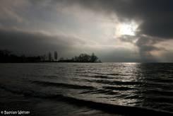 Die Sonne bricht durch die Wolken über dem Bodensee bei der Insel Reichenau