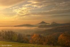Ein Morgen im Herbst: Der Ausblick vom Hegaublick zeigt viel Nebel in den Tälern, einzelne Gipfel der Hegauberge ragen dabei aus dem Nebel und im Hintergrund erkennt man andeutungsweise die Alpen