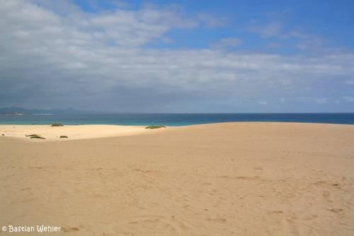 Im Norden von Fuerteventura bei Corralejo gibt es direkt am Meer eine riesige Sandwüste und noch wunderschöne Strände, im Hintergrund kann man die Insel Lanzarote erkennen