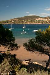 Mehrere kleinere Boote in der Bucht von Agay, im Hintergrund an den Hängen liegt die Ferienanlage Cap Esterel mit Golfanlage und Ferienwohnungen