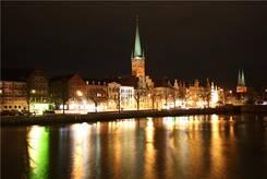Nächtlicher Blick über die Stadt-Trave Richtung Holstenbrücke, im Hintergrund Petri Kirche und Dom