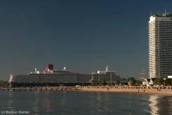 Nur sehr langsam kann die Queen Elizabeth die Trave befahren und wirkt neben dem hohen Maritim Hotel keinesfalls klein