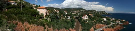 Panorama der Küste bei Le Trayas, links die roten Felsen des Esterel mit den Häusern des Ortes an ihren Hängen, dann die Bahnlinie Richtung Nizza sowie die Küstenstraße Corniche d'Or und schließlich rechts das Mittelmeer