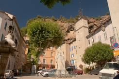 Platz in Cotignac mit Rathaus, Uhrenturm, uralter riesiger Platane und Brunnen vor der Felswald aus Tuffstein im Hintergrund