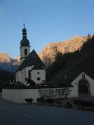 Ramsau: Die Pfarrkirche St. Sebastian mit den vom Sonnenaufgang beleuchteten Bergen im Hintergrund