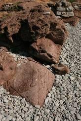 Rote Felsen des Esterel Gebirges und graue Kieselsteine am Plage du Débarquement