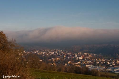 Sonnenschein in Stockach, über den Hügeln im Hintergrund und dem Bodensee liegt dicker Nebel