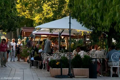 Terrassenförmige Gasse mit mehreren Restaurants an einem Sommerabend in Gassin