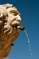 Wasser speiender steinerner Kopf, eine weitere Figur an der Fontaine du Cormoran